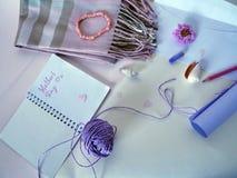 紫外纸、一个白色信封、一支红色铅笔和一只淡色蜡笔卷祝贺的在母亲` s天 库存图片