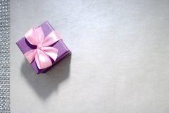 紫罗兰色有一把弓的礼物美丽的欢乐纸板小礼物盒在浅灰色的背景 免版税库存图片