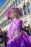 紫罗兰色服装的妇女在威尼斯狂欢节2018年 免版税库存照片