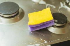 紫罗兰色-与金属煤气炉的黄色海绵 清洗土与与泡沫的一块海绵 免版税库存照片