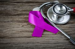 紫色丝带了悟和听诊器在木背景 免版税库存图片