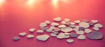 紫色和白色在流行粉红背景与温暖的轻的华伦泰,爱的毛毡心脏 库存照片