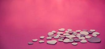紫色和白色在流行粉红背景与温暖的轻的华伦泰,爱的毛毡心脏 免版税库存照片