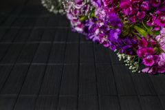 紫色和紫罗兰色花对角框架在黑暗的木backg的 免版税库存图片