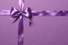 紫色在紫色背景隔绝的弓和丝带 图库摄影
