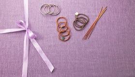 紫色布料背景包扎与与弓的丝绸丝带 免版税库存图片