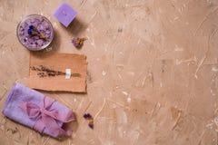 紫色海盐,在具体棕色背景的一块木梳子毛巾 免版税库存照片
