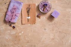 紫色海盐,在具体棕色背景的一块木梳子毛巾 库存图片