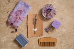 紫色海盐,在具体棕色背景的一块木梳子毛巾 库存照片