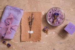 紫色海盐,在具体棕色背景的一块木梳子毛巾 图库摄影