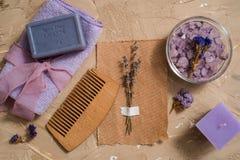 紫色海盐,在具体棕色背景的一块木梳子毛巾 免版税库存图片