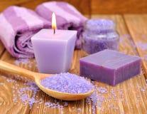 紫色海运盐和一个灼烧的蜡烛 免版税图库摄影