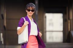 紫色燃烧物和太阳镜的年轻时装业妇女走在城市街道的 库存照片