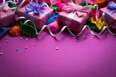 紫色物质五颜六色的气球飘带五彩纸屑四箱子礼物顶视图舱内甲板欢乐背景放置拷贝空间 图库摄影