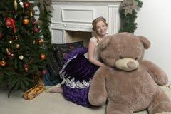 紫色礼服的女孩在与一头巨大的熊的圣诞节 免版税库存图片