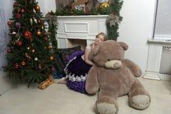 紫色礼服的女孩在与一头巨大的熊的圣诞节 库存图片