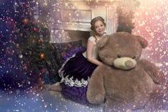 紫色礼服的女孩在与一头巨大的熊的圣诞节 库存照片
