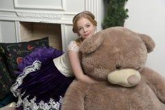 紫色礼服的女孩在与一头巨大的熊的圣诞节 免版税库存照片