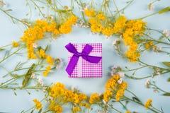 紫色礼物盒围拢与在轻的薄荷的背景的黄色和白色小的花 免版税库存照片