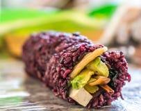 紫色米寿司卷用豆腐芒果和鲕梨素食主义者寿司膳食的 库存图片