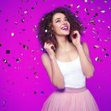 紫色背景的美丽的微笑的少妇与飞行c 库存照片