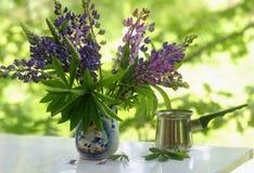 紫色花和咖啡在绿色背景 库存照片