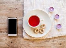紫色芳香蜡烛、杯子、百吉卷和电话在一张木桌上 免版税图库摄影