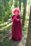 紫色衣裳的年轻巫婆在有一个蜡烛的森林里在他的手上 库存照片