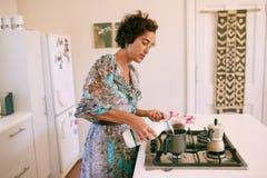 繁忙成熟的妇女在家做她的早晨咖啡 库存图片