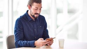 繁忙时髦的人看他的电话屏幕,当发短信时 图库摄影
