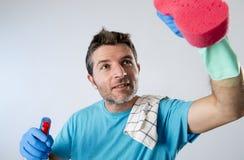 繁忙的与浪花瓶和海绵洗涤的玻璃的丈夫微笑的愉快的做的房子清洁 库存图片