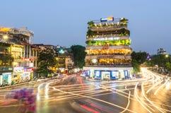 繁忙的交通晚上视图在有许多摩托车和车的一个交叉点在河内,越南的首都 免版税库存照片