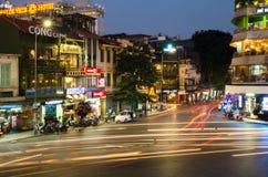 繁忙的交通晚上视图在有许多摩托车和车的一个交叉点在河内,越南的首都 免版税库存图片