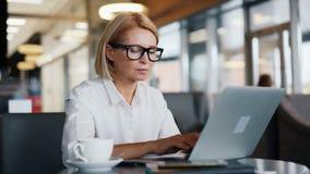 繁忙的企业家资深妇女与输入现代咖啡馆的膝上型计算机一起使用 股票录像