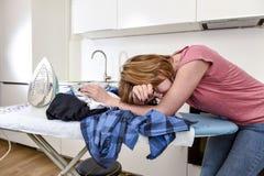 繁忙的使用铁地方教育局的主妇电烙的衬衣懒惰在家厨房 库存图片