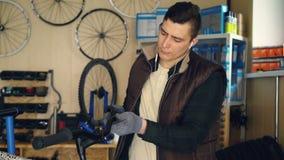 繁忙的军人在车间时拆卸周期把手和清洗的部分与布料,当为自行车服务 Youg 影视素材