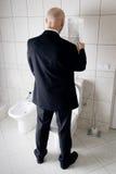 繁忙的厕所人新闻读取 免版税库存照片