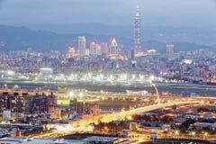 繁忙的台北市、基隆河, Dazhi桥梁,松山机场& 101塔全景鸟瞰图在信义区黄昏的 库存图片