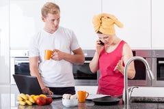 繁忙的夫妇早晨在厨房里 库存照片