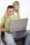 繁忙的夫妇膝上型计算机年轻人 免版税库存图片