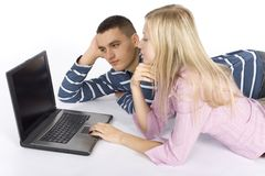 繁忙的夫妇膝上型计算机年轻人 免版税库存照片