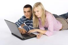 繁忙的夫妇膝上型计算机年轻人 库存照片