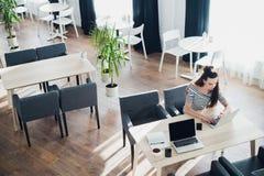 繁忙的妇女她的工作为最后期限做准备 在一个咖啡馆的有吸引力的女性开会与膝上型计算机和电话 免版税库存图片