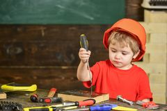 繁忙的孩子与螺丝刀一起使用 橙色盔甲约束螺丝的被集中的男孩到木块里 库存图片