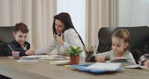 繁忙的成熟母亲有在电话的一次交谈,当做与她的三个孩子的家庭作业在客厅时 股票视频