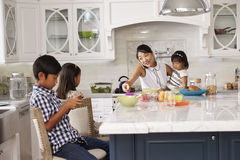 繁忙的早餐的母亲组织的孩子在厨房里 库存图片