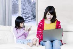 繁忙的母亲和她的孩子有膝上型计算机的 免版税库存照片