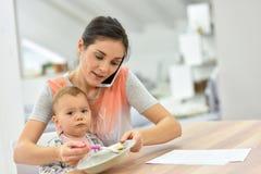繁忙的母亲喂养她的婴孩和谈话在电话 免版税图库摄影