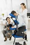 繁忙的行政获得的按摩在办公室 免版税图库摄影
