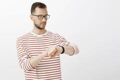 繁忙的被聚焦的商人Wiast-up射击在玻璃的,看数字手表,检查时间,当等待时 图库摄影